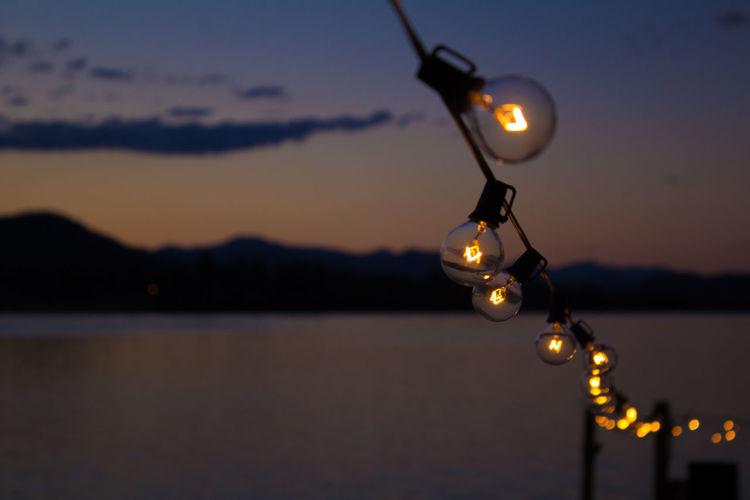 Row of illuminated light bulbs over river against sky