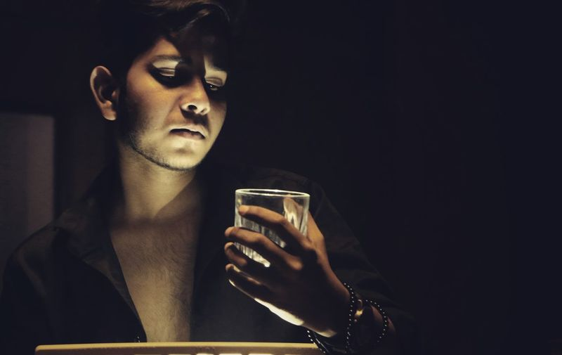 Young man holding drinking glass in darkroom