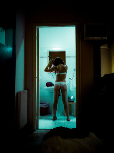 Rear view of woman standing against door at badroom home