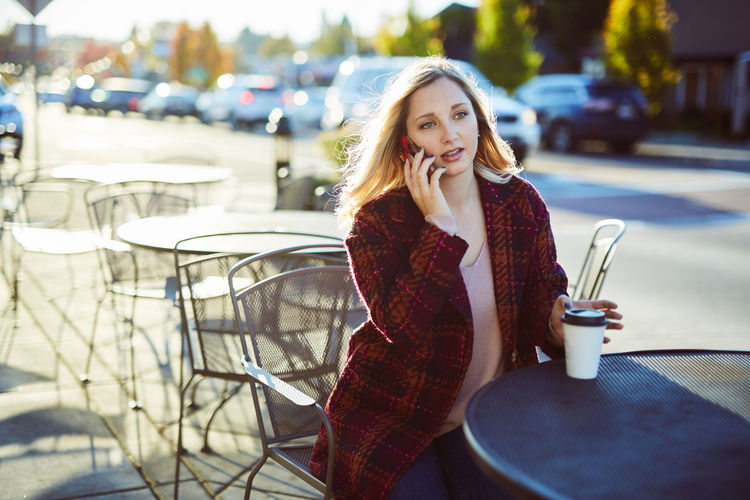 Beautiful Woman Blond Hair Cafe Casual Clothing City Coffee Cup Day Drink Fashion Focus On Foreground Front View Leisure Activity Lifestyles Looking At Camera Mobile Phone One Person Outdoors Portrait Real People Sidewalk Cafe Sitting Smiling Wireless Technology Young Adult Young Women