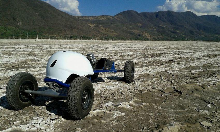 Motorcycle on sand against mountain range
