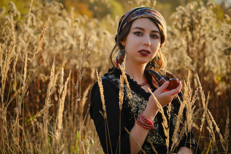 Young gypsy woman smoking pipe in autumn dry grass, looking at camera