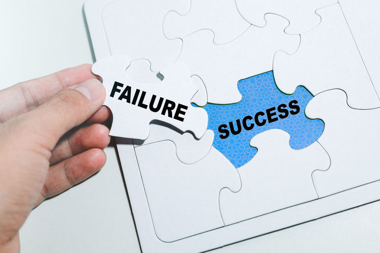 FAILURE over SUCCESS word on blue surface with flare surrounds with white jigsaw puzzle. - Image Human Hand Hand Jigsaw Piece Human Body Part Puzzle  One Person Indoors  Finger Leisure Activity Human Finger Communication Real People Text Holding Connection Body Part High Angle View Solution Western Script Failure  Success