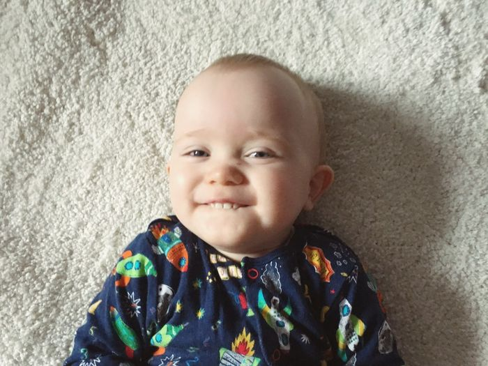 High angle portrait of cute smiling baby boy lying on bed at home