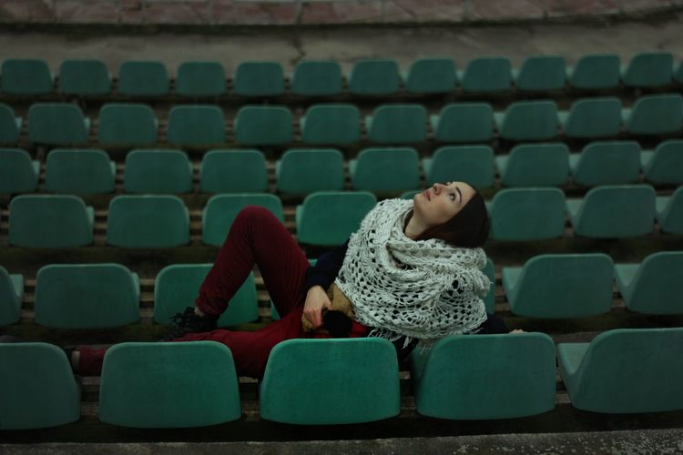 Woman Reclining On Chairs At Stadium