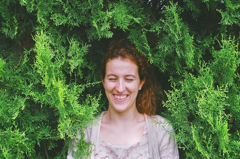 Cheerful woman with eyes closed standing by plants