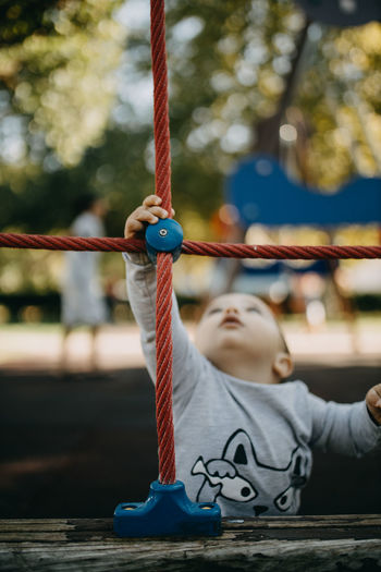 Low angle view of swing hanging on rope at playground
