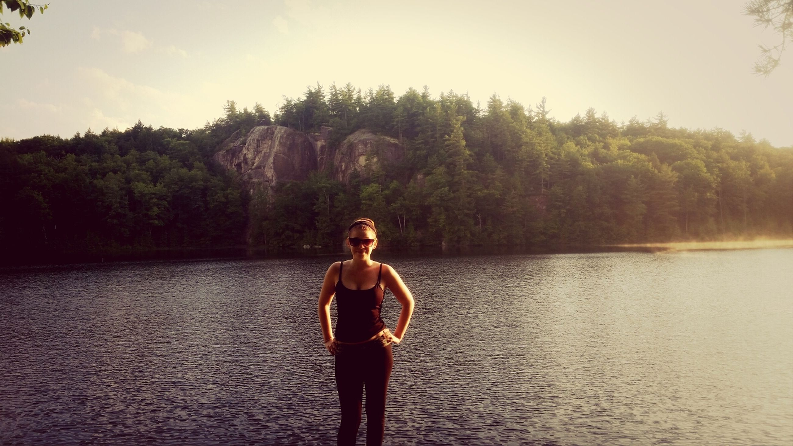 water, standing, lifestyles, tranquil scene, tranquility, tree, casual clothing, leisure activity, scenics, beauty in nature, young adult, nature, lake, full length, person, sky, mountain, three quarter length