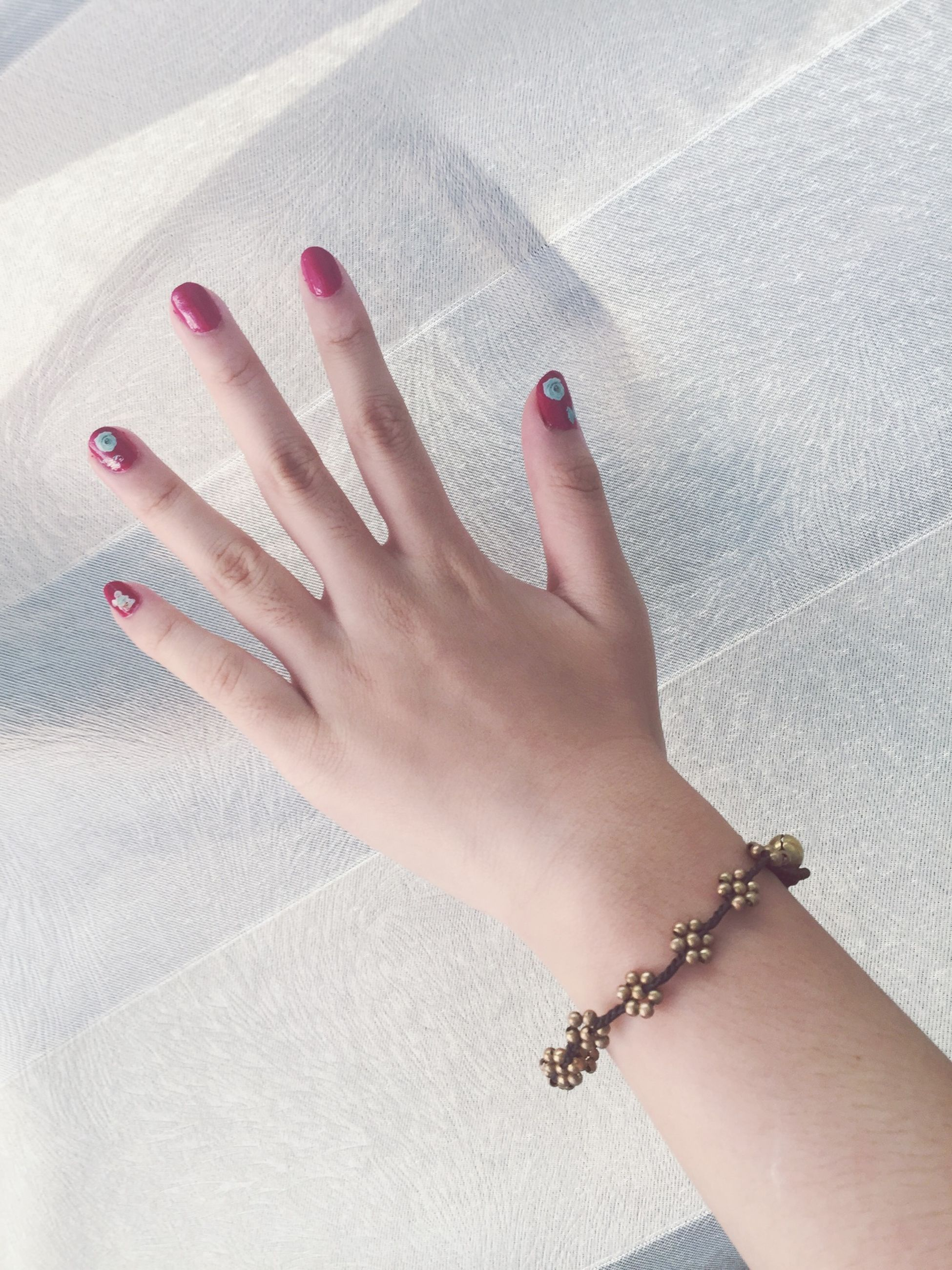 person, part of, human finger, personal perspective, cropped, lifestyles, indoors, leisure activity, holding, unrecognizable person, wall - building feature, touching, close-up, nail polish, high angle view