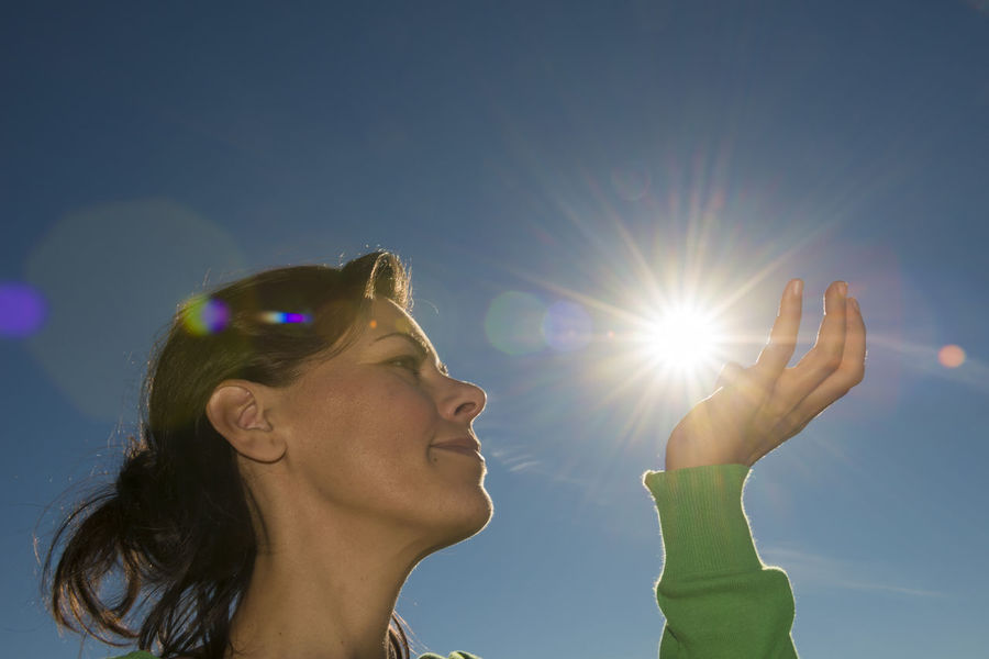 Woman Holding up the Sun Adult Backlit Careful Clear Sky Color Concept Creativity Full Frame Hold Holding Human Hand Lens Flare Low Angle View One Person One Woman Only Positive Emotion Positive Energy  Power Power In Nature Profile Side View Sun Sunbeam Sunshine Woman