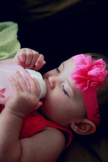 Close-Up Of Baby Girl Drinking Milk While Napping On Bed