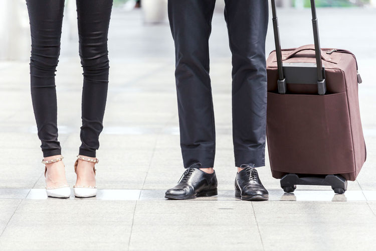 Business people with luggage in the city Adult Airport Body Part Business Business Person Day Group Of People Human Body Part Human Foot Human Leg Human Limb Low Section Luggage Men Motion People Shoe Standing Suitcase Travel Waiting Walking Women