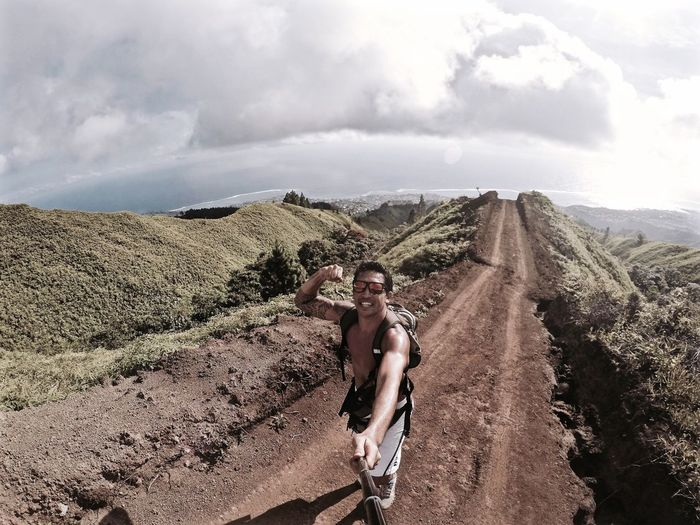 Happy hiker with monopod showing bicep on dirt road against sky