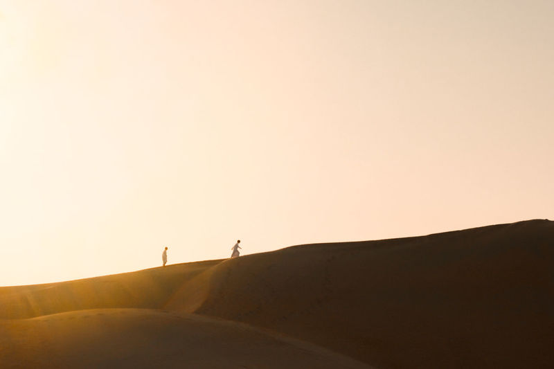 Silhouette person standing on desert against clear sky