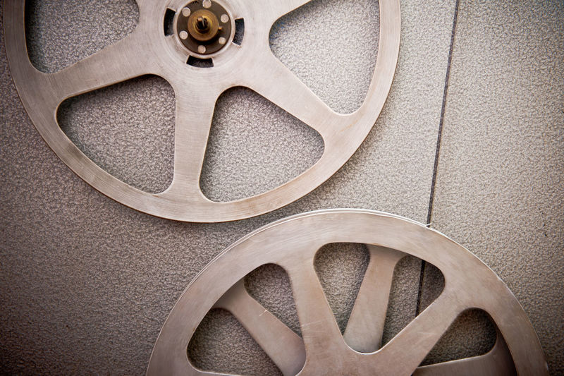 Couple of steel movie reel on vintage cinema projector 35mm Cinema Close-up Empty Film Filmstrips MOVIE No People Projector Reel Reels Round Steel Wheel