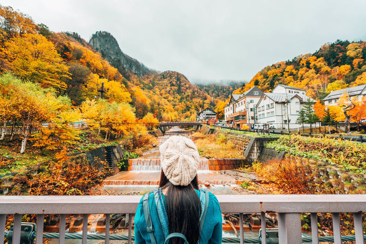 Daisetsuzan Autumn Change Real People Tree One Person Rear View Plant Nature Lifestyles Women Leisure Activity Beauty In Nature Day Architecture Orange Color Mountain Adult Sky Built Structure Outdoors Warm Clothing Autumn Collection Hairstyle