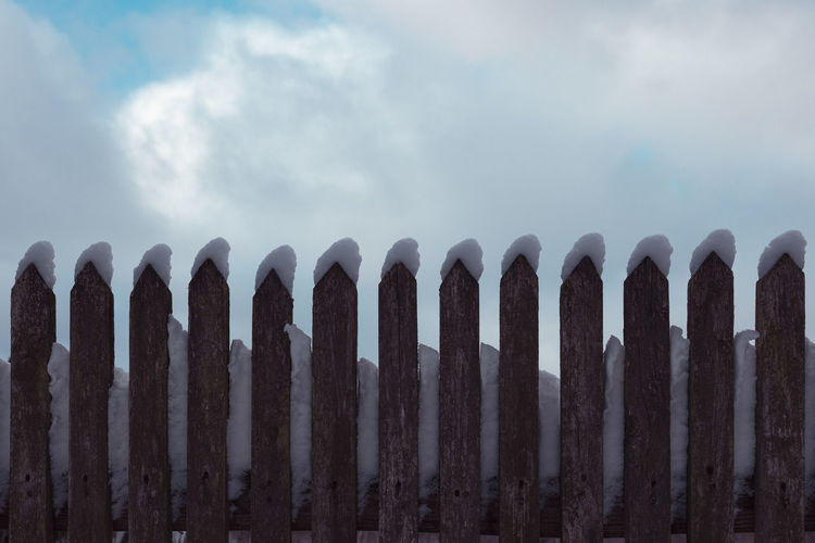 Low angle view of fence against sky during foggy weather