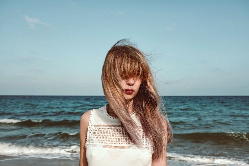 Beautiful woman with tousled hair standing on sea shore against sky