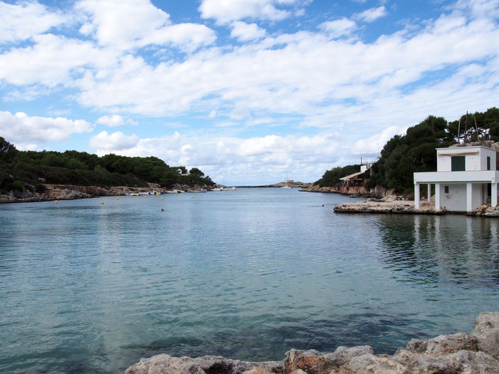 a view of Cala Santandria in a bright cloudy day in Menorca Spain Cuitadella Cale Santandria Bay Resort Beach Menorca Travel Destination Water Cloud - Sky Sky Scenics - Nature Beauty In Nature Nature Sea Tranquility Day No People Built Structure Waterfront Outdoors Building Exterior Idyllic