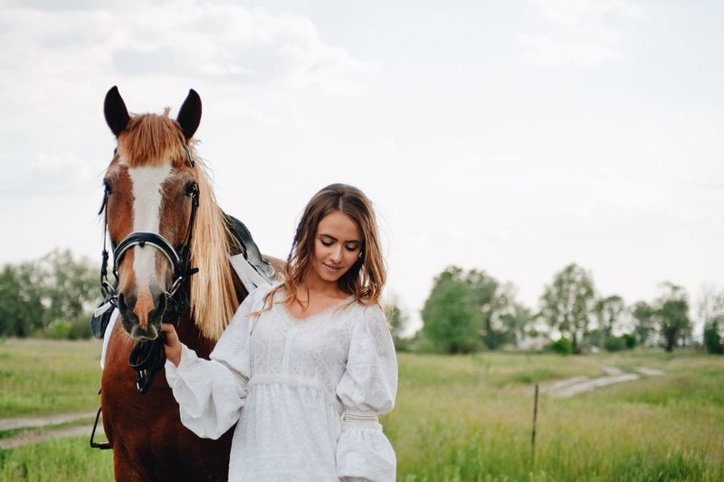 Young woman with horse on field
