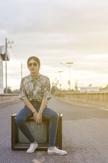 Young woman enjoying sitting on an old television. Beautiful Woman Casual Clothing Day Fashion Focus On Foreground Front View Full Length Glasses Hairstyle Leisure Activity Lifestyles Looking At Camera Nature One Person Outdoors Portrait Real People Sitting Sky Young Adult Young Women