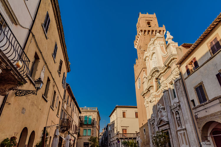 Low angle view of pitigliano cathedral against clear blue sky during sunny day