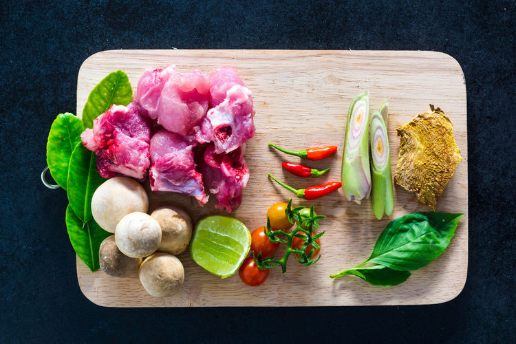 High angle view of raw vegetables along with meat on cutting board
