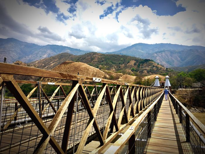 Mountain Range Sky Railing Cloud - Sky Bridge - Man Made Structure Wood - Material Outdoors Nature Beauty In Nature Day The Way Forward Scenics One Person Landscape Footbridge Full Length Real People Water Tree Beautiful Colombia Antioquia Colombia Colombia Is Passion