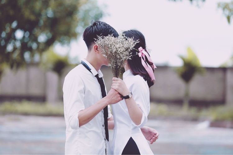 Side view of couple holding bouquet