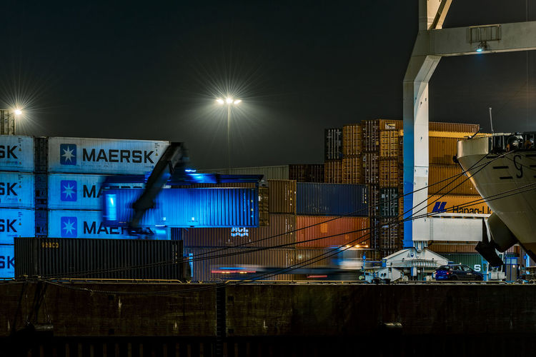 Loading Container Container Ship Artificial Light Nightphotography Container Bridge Long Exposure Night Illuminated Transportation Industry No People Sky Outdoors Freight Transportation Lighting Equipment Lens Flare Business City Light - Natural Phenomenon Cargo Container Construction Industry Sign