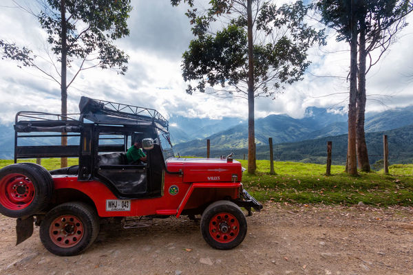 SALENTO, COLOMBIA - JUNE 7: A red jeep parked on a rural road outside of Salento, Colombia on June 7, 2016. Cloud Colombia Farm Hiking Palm Pasture Quindío Red Rural Tree Trip Andean Cauca Colombian  Countryside Forest Hike Jeep Landscape Outdoors Quindío Salento Tolima Trek Wax