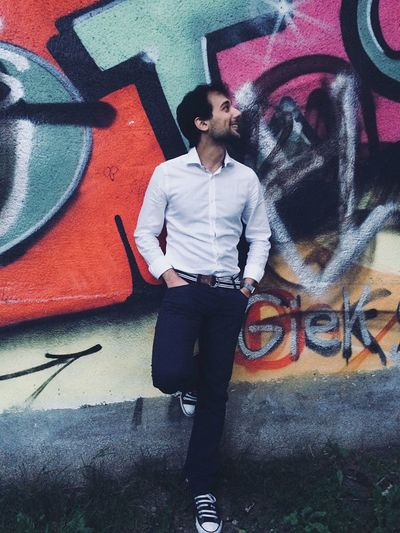 Full length of young man standing against graffiti wall