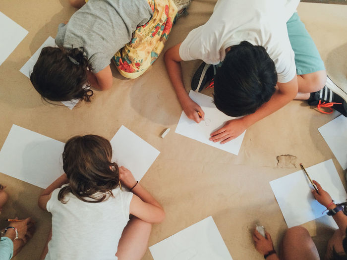 High Angle View Of Children Drawing On Paper Indoors