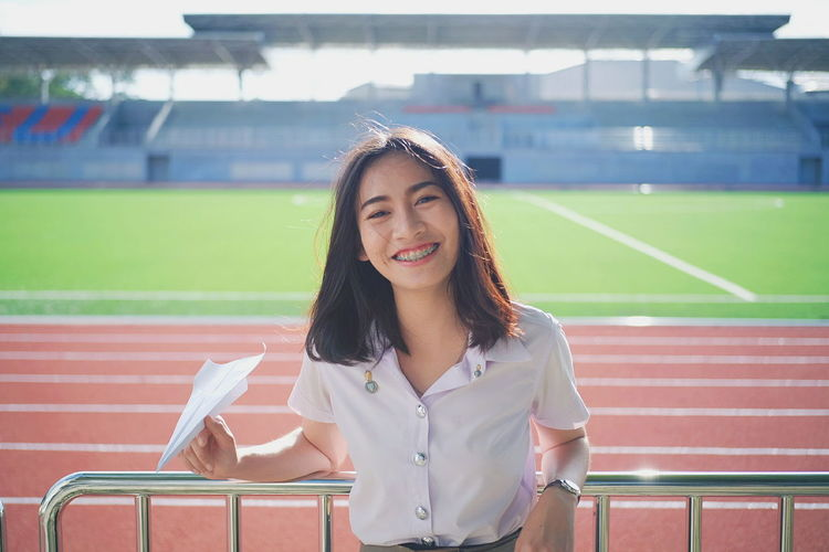 Portrait of smiling young woman holding paper airplane while standing in stadium