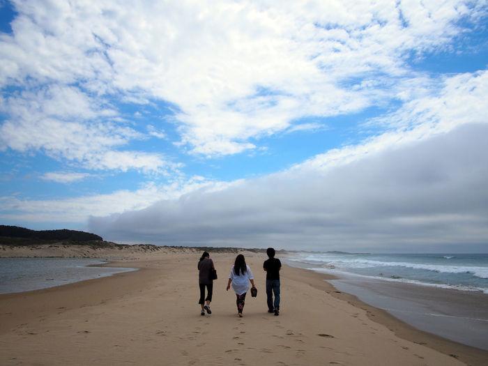 Rear view of men walking on beach against sky