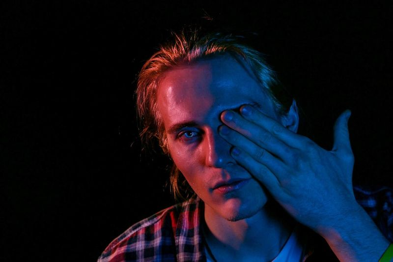 Portrait Of Man With Eye Covered By Hand In Darkroom