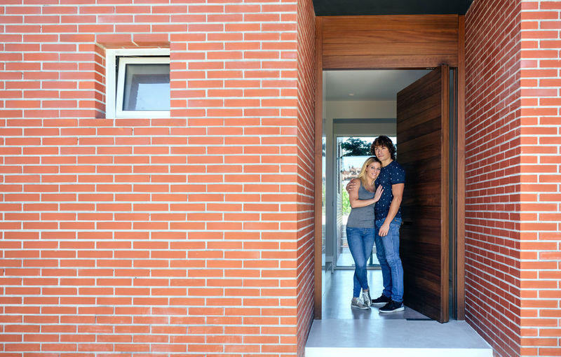 Loving Couple Standing At Doorway