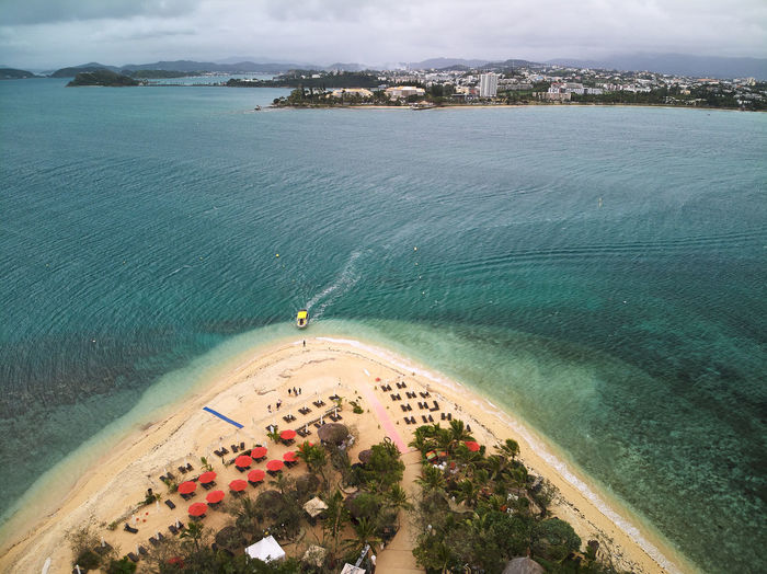 High angle view of beach and sea with boat fetching tourists