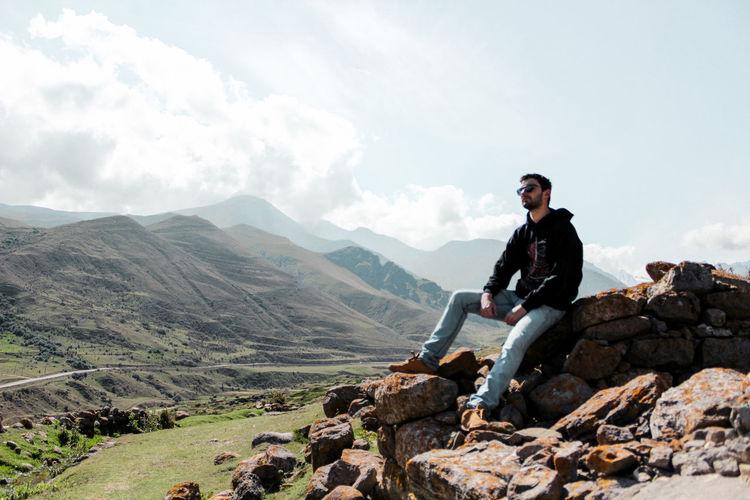 Portrait of man on rock against sky