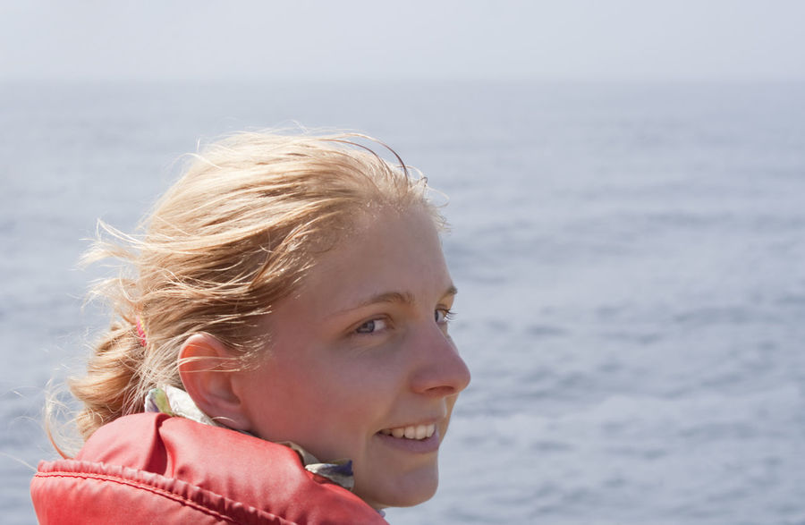 Young Woman with red Floatation Suit - Portrait on a Whale Watching Tour Adventure Blond Hair Canada Close-up Confidence  Exploring Floatation Suit Fun Happy Head And Shoulders Headshot Joy Life Jacket Life Vest One Young Woman Only Outdoors Portrait Profile Protective Sportswear Real People Sea Smile Teenage Girls Water Young Women