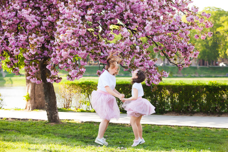 Full length of girls playing by flowering tree