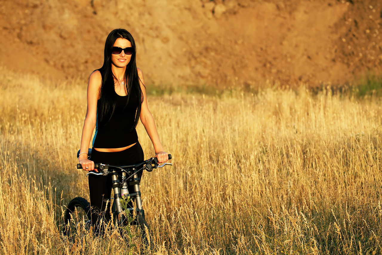 young adult, leisure activity, smiling, front view, bicycle, happiness, one person, lifestyles, young women, portrait, looking at camera, real people, casual clothing, beautiful woman, outdoors, field, grass, cheerful, nature, standing, day, adult, people