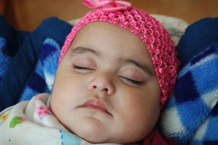 Portrait of cute baby girl sleeping on bed