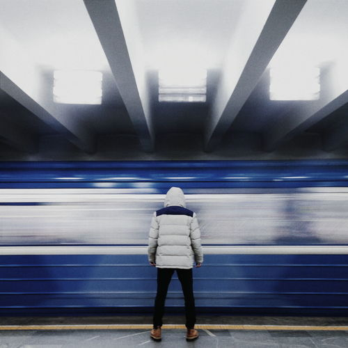 Rear View Of Man Standing Against Train Moving At Illuminated Subway Station
