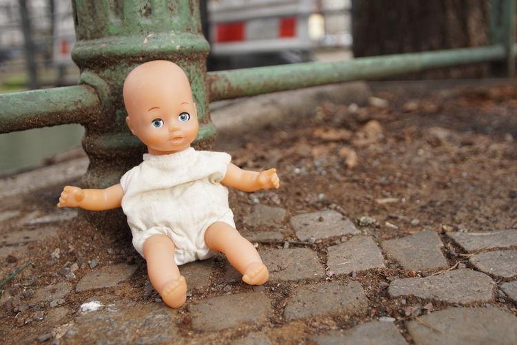 Doll on footpath by railing