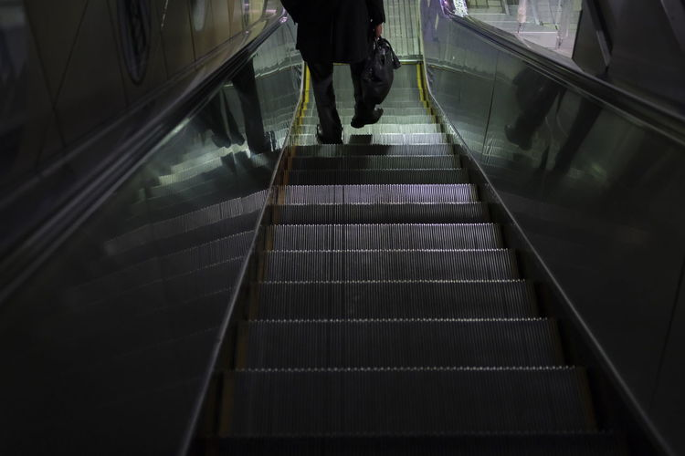 Low section of man walking on escalator