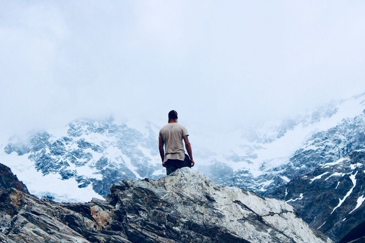 Rear view of man on snowcapped mountain against sky