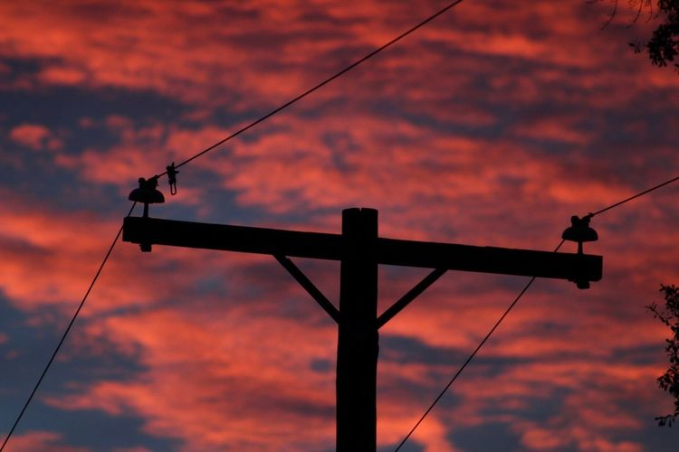Low angle view of silhouette crane against cloudy sky during sunset