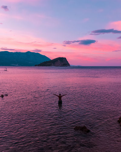 Rear view of shirtless man in sea against sky during sunset