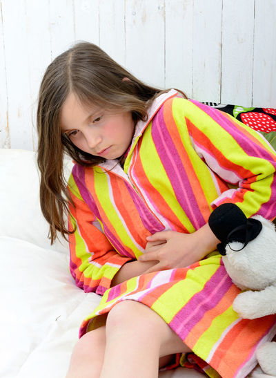 Girl holding stomach while sitting on bed